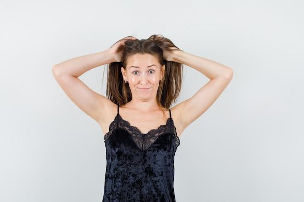Giovane donna che tiene le mani nei capelli in canottiera nera e sembra divertente