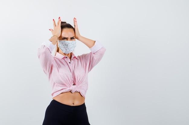 Giovane donna che tiene le mani sulla testa in camicia, pantaloni, mascherina medica e sembra infastidita. vista frontale.