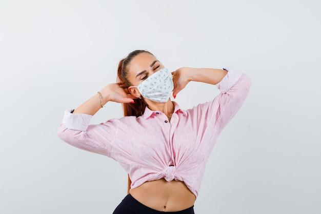 Giovane donna che tiene le mani sulla testa in camicia, pantaloni, mascherina medica e guardando fiducioso, vista frontale.
