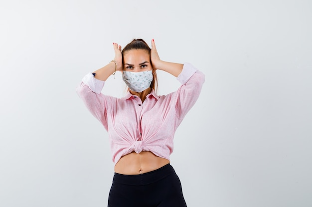 Giovane donna che tiene le mani sulla testa in camicia, pantaloni, mascherina medica e sguardo smemorato, vista frontale.