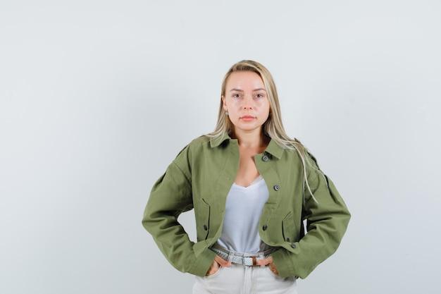 Молодая женщина, взявшись за руки в кармане, позирует в куртке, блузке и выглядит уверенно, вид спереди.