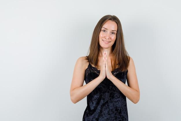 Молодая женщина, взявшись за руки в молитвенном жесте в черной майке и выглядя весело