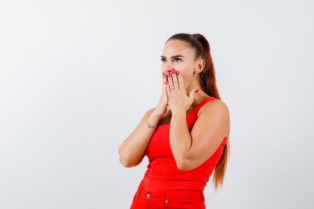 Giovane donna che tiene le mani sulla bocca in canottiera rossa, pantaloni e guardando perplesso. vista frontale.