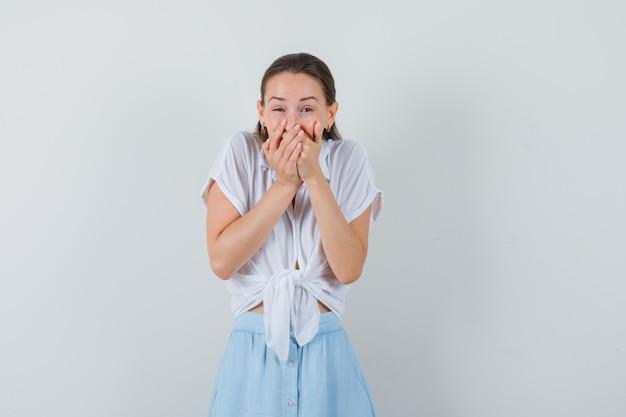 Giovane donna che tiene le mani sulla bocca mentre rideva in camicetta e gonna vista frontale.