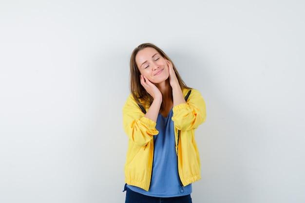 Молодая женщина держится за щеки, закрывает глаза в футболке, куртке и выглядит мирно. передний план.