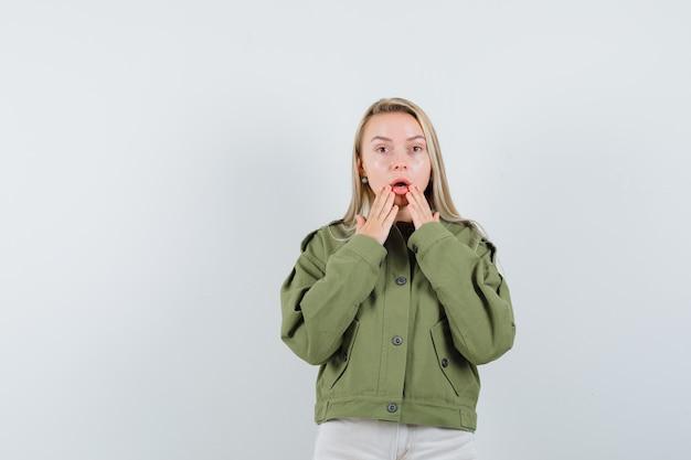 젊은 여성 녹색 재킷, 청바지에 떨어진 턱에 손을 잡고 불안을 찾고. 전면보기.