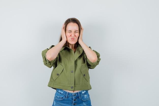 ジャケット、ショートパンツで耳に手をつないで、イライラして見える若い女性、正面図。