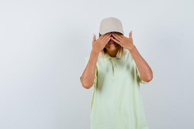 T- 셔츠, 모자에 눈에 손을 잡고 귀여운, 전면보기를 찾고 젊은 여성.