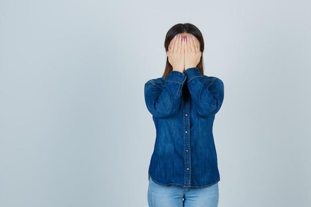 Молодая женщина, держащая руки на лице в джинсовой рубашке и джинсах и выглядящая задумчивой