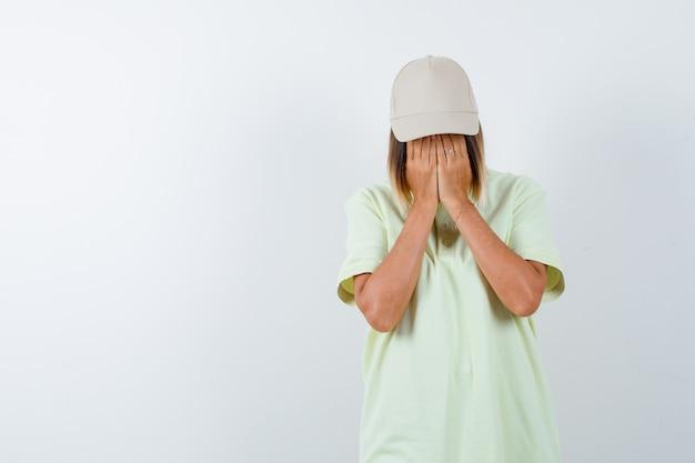 젊은 여성 t- 셔츠, 모자에 얼굴에 손을 잡고 무서 워보고. 전면보기.
