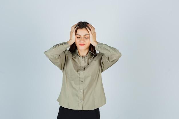 젊은 여성 셔츠에 머리에 손을 잡고 피곤 찾고