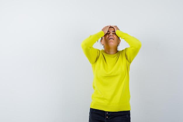 セーター、デニムスカートで頭に手をつないで、忘れて見える若い女性