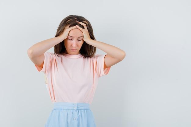 Tシャツ、スカートで頭に手をつないで、疲れ果てているように見える若い女性。正面図。