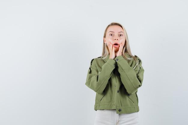 젊은 여성 재킷, 블라우스에 그녀의 떨어진 턱에 손을 잡고 불안, 전면보기를 찾고.