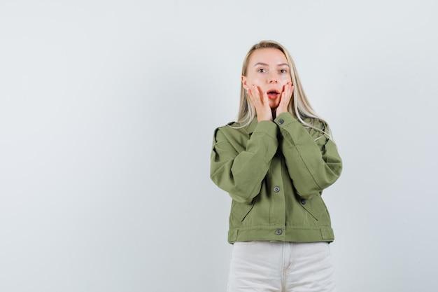 젊은 여성 재킷, 블라우스에 그녀의 드롭 턱에 손을 잡고 무서 워, 전면보기를 찾고. 텍스트를위한 공간