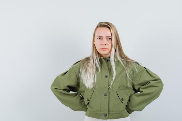 緑のジャケットで彼女の腰に手をつないで、緊張しているように見える若い女性、正面図。