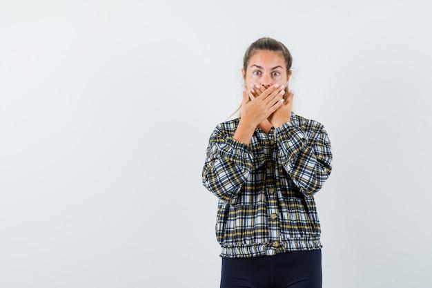 シャツ、ショートパンツで口に手をつないで、ショックを受けた若い女性。正面図。