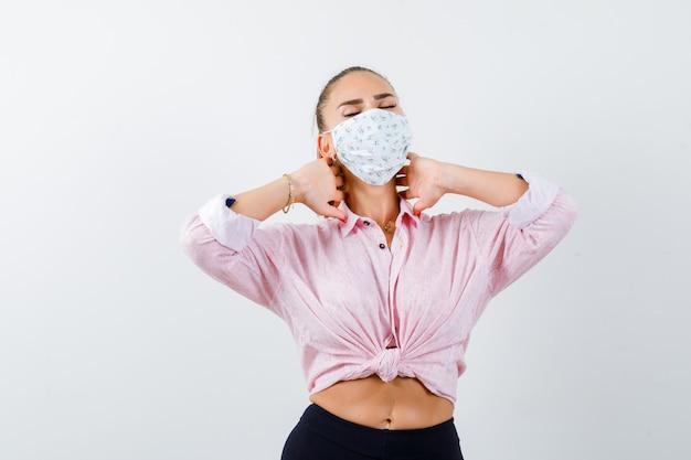 Молодая женщина, держащая руки на шее в рубашке, штанах, медицинской маске и выглядящая измотанной, вид спереди.