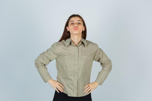 젊은 여성은 허리에 손을 잡고 셔츠, 치마에 입술을 내밀고 귀엽게 보이는 전면 보기.