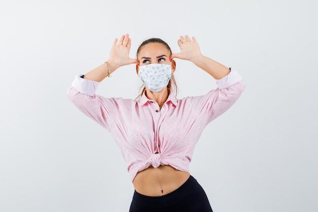 셔츠, 바지, 의료 마스크에 귀로 머리 위로 손을 잡고 웃기는 찾고 젊은 여성. 전면보기.