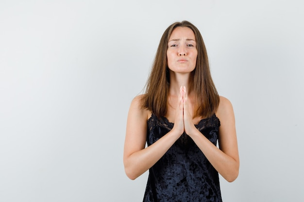 Young female holding hands in praying gesture in black singlet and looking hopeful