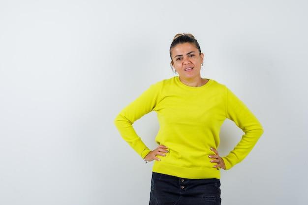 Giovane donna che si tiene per mano sulla vita in maglione, gonna di jeans e sembra carina