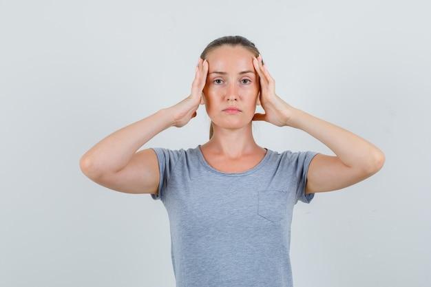 灰色のtシャツと手で頭を抱えて、疲れているように見える若い女性、正面図。