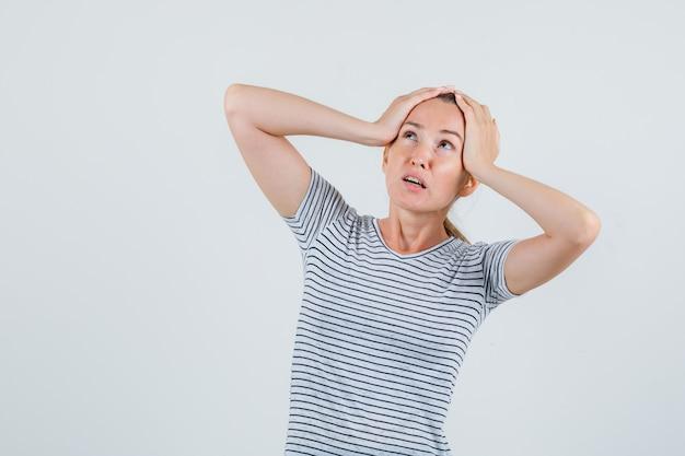 Giovane donna che tiene la testa con le mani in maglietta a righe e guardando preoccupato. vista frontale.