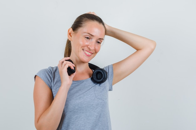 灰色のtシャツでヘッドフォンを保持し、嬉しそうに見える若い女性、正面図。