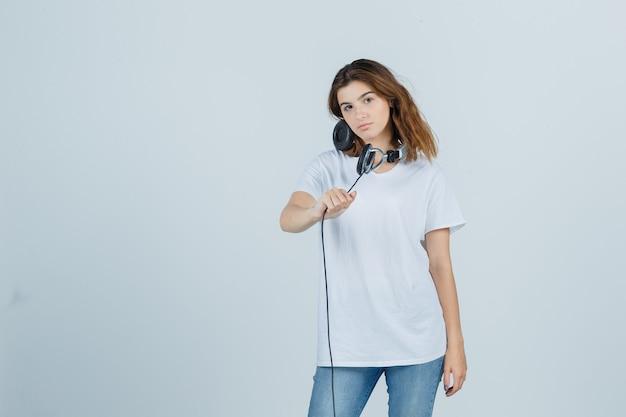白いtシャツ、ジーンズ、魅力的な正面図でヘッドフォンを保持している若い女性。