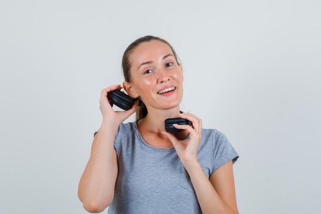 Молодая женщина держит наушники возле уха в серой футболке, вид спереди.