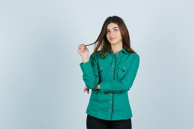 녹색 셔츠에 손가락으로 그녀의 밤나무 머리를 들고 쾌활한, 전면보기를 찾고 젊은 여성.
