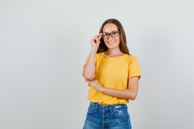 Tシャツ、ショートパンツ、陽気に見える彼女の眼鏡を保持している若い女性