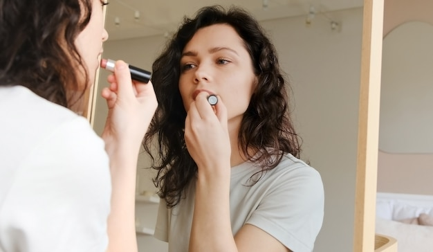 Young female holding lipstick in her hands and paints lips prepare getting ready in the morning. woman doing makeup. get ready for a date.