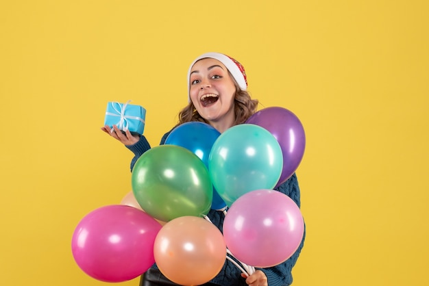 Young female holding little present and balloons on yellow