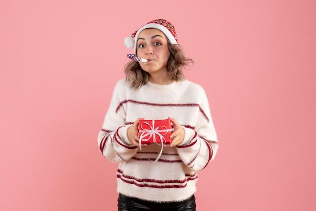 핑크에 작은 선물을 들고 젊은 여성