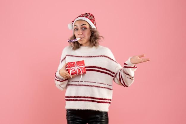 ピンクに少しプレゼントを持っている若い女性