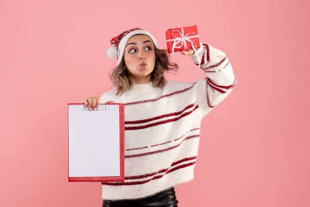 Young female holding little xmas present and note on pink