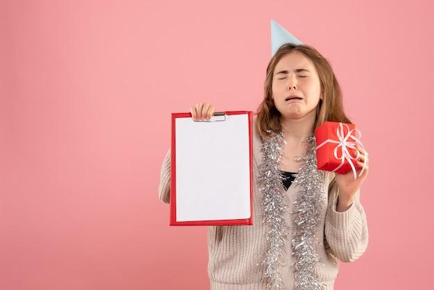 Giovane femmina che tiene poco regalo di natale e nota sul rosa