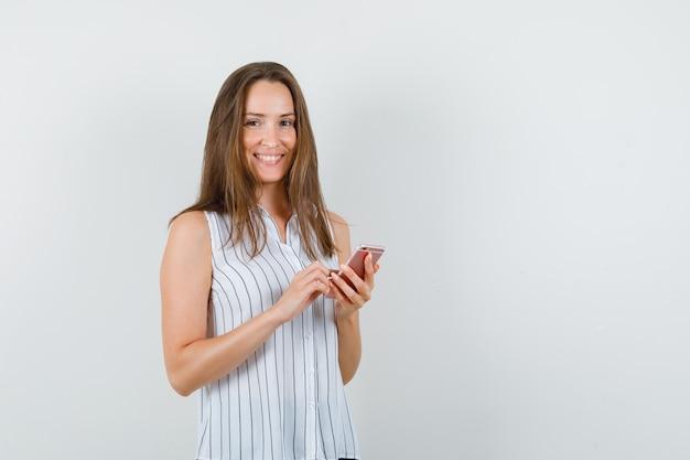 Tシャツに携帯電話を持って元気そうな若い女性。正面図。