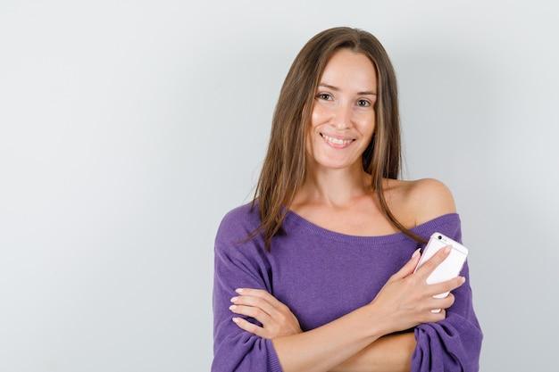 Молодая женщина держит мобильный телефон в фиолетовой рубашке и выглядит веселым. передний план.