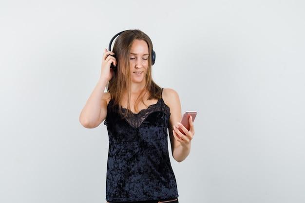 Giovane femmina che tiene il telefono cellulare, ascoltando la musica in singoletto nero