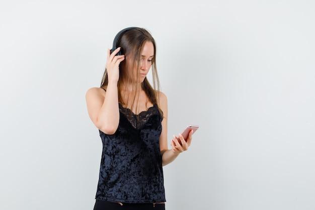 Молодая женщина держит мобильный телефон, слушает музыку в черном синглете