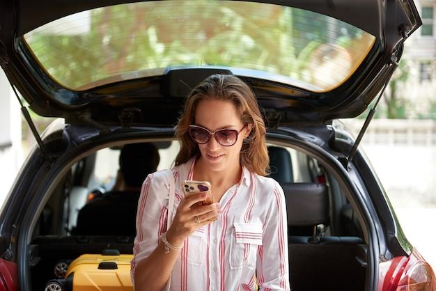 Молодая женщина держит мобильный телефон, сидя в машине обратно