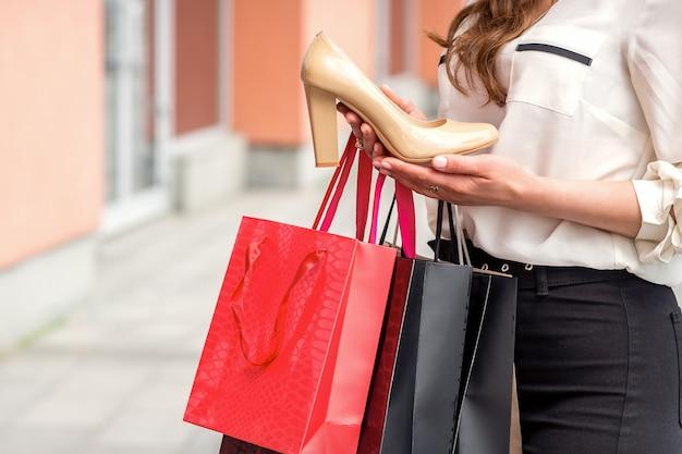 屋外のショッピングモールの近くでバッグを持って立って買い物をした後、新しいハイヒールの靴を保持している若い女性