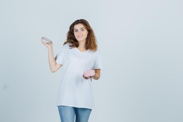 젊은 여성 지주 흰색 t- 셔츠, 청바지에 선물 상자를 열고 기쁜 찾고. 전면보기.