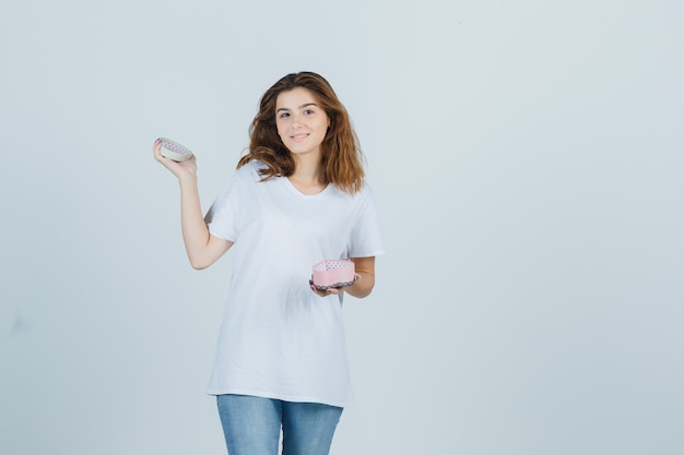Young female holding opened gift box in white t-shirt, jeans and looking glad. front view.