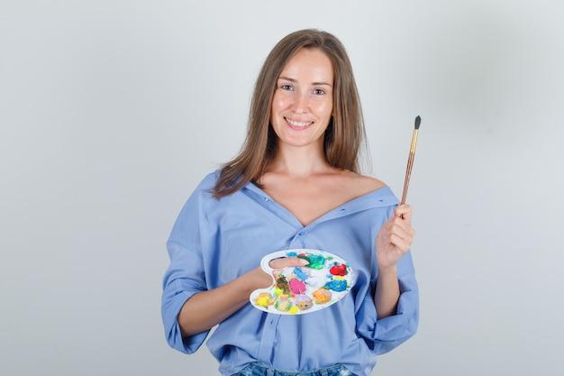 Молодая женщина держит кисть и палитру в рубашке, шортах и выглядит весело