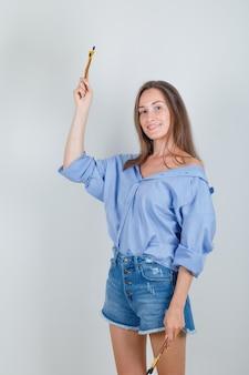 Молодая женщина держит кисти и улыбается в рубашке