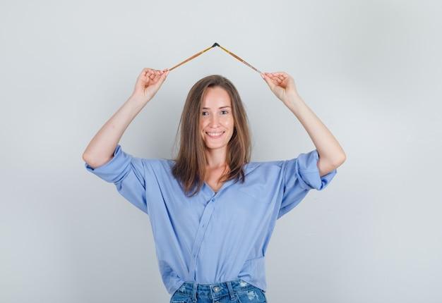 Giovane donna che tiene i pennelli sopra la testa in camicia, pantaloncini e sembra allegro